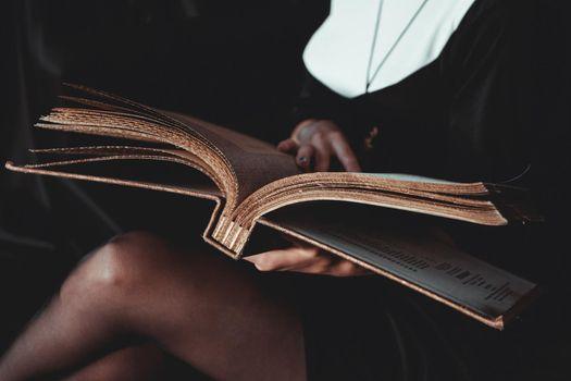 Nun in religion black suit holds Bible. Religion concept