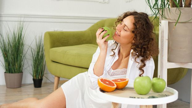 Young woman eating green apple at home. Healthy nutrition, diet food concept
