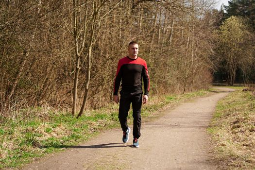 A man in sportswear on a forest path. A man after morning jog walks in the woods