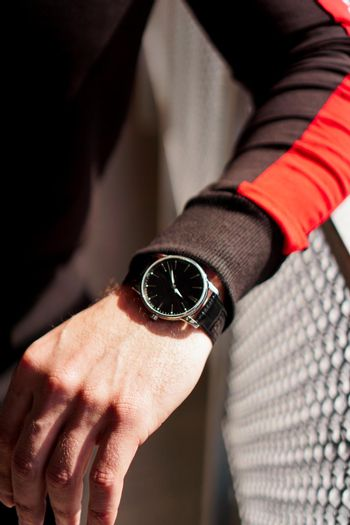 A man's hand in comfortable sportswear and an expensive watch on his wrist