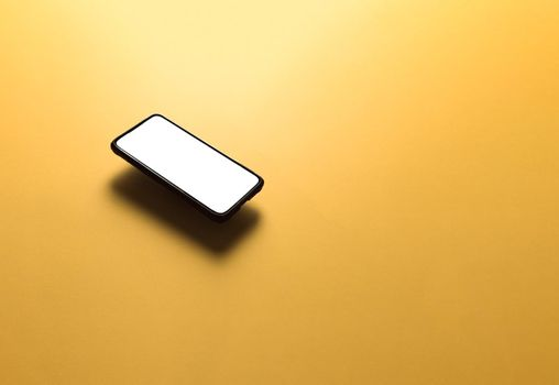 Minimalistic mock up flat image design with a floating mobile phone with copy space and white scree to write over it over a flat yellow background