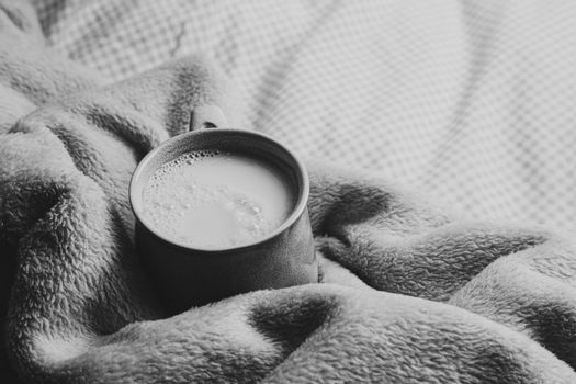 A cup of milk over a cozy blanket