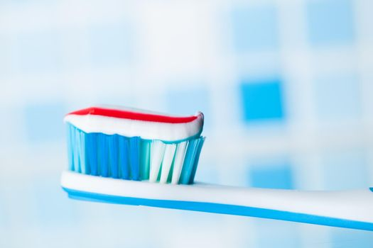 blue toothbrush with red stripe toothpaste