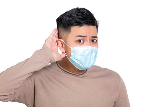 Young man wearing medical mask with hand over ear listening and hearing to rumor or gossip