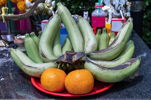 Raw bananas and oranges on a red tray For worship The thao maha phrom shrineis.
