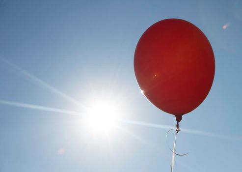 red balloon and blue sky background with sun, symbol for joy and happiness