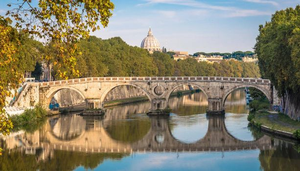 Bridge on Tiber river in Rome, Italy. Vatican Basilica cupola in background with sunrise light.