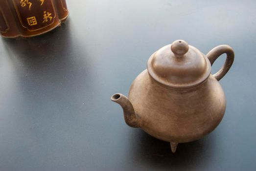 Tea and tea storage placed directly across the black table