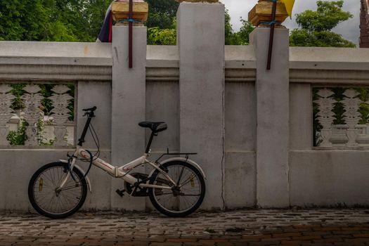 bangkok,Thailand - jun 29, 2019 : White bike parked on the sidewalk beside the temple wall.