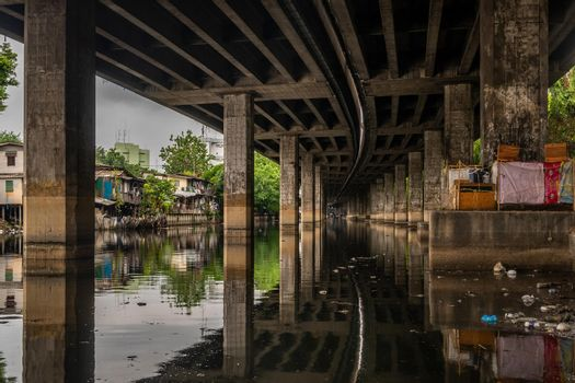 bangkok,Thailand - jun 30, 2019 : Khlong Toei Expressway over the Phra Khanong canal and house with the shadow of the bridge on the canal.