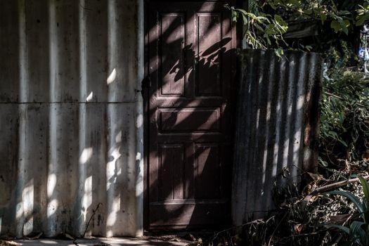 A tree shadow is shining Old rusty zinc sheet wall with old wooden door, Light and Shadow