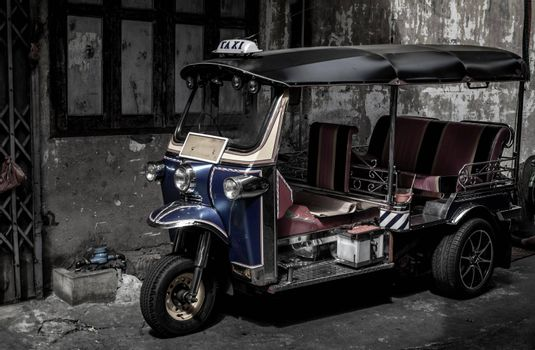 Bangkok, Thailand - Dec 7, 2019 : Famous blue Tuk Tuk, Thai traditional taxi with an old ancient wall behind.