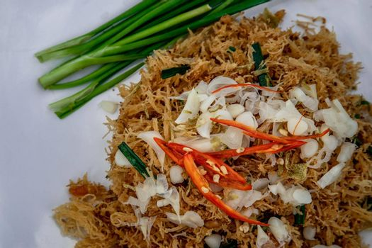 Asian eating food, Mee Grob is an sweet and sour crispy noodles, made from Thai rice noodle with sweet and sour sauce on white plate, Sweet & Sour Crispy Rice Noodles, Close up.