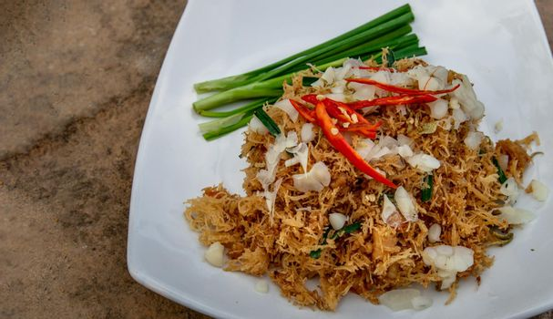 Asian eating food, Mee Grob is an sweet and sour crispy noodles, made from Thai rice noodle with sweet and sour sauce on white plate, Sweet & Sour Crispy Rice Noodles, Oblique view from the top.