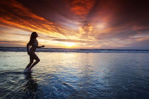 Woman running by the ocean beach
