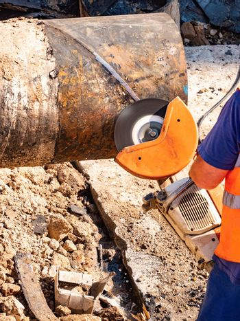 Worker cutting large metal pipe with industrial grinder in  trench