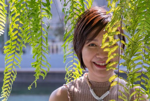 Portrait of smiling of happy beauty asian young asian woman enjoy and smiling behind green ferns leaves. Happy woman in nature concept, Selective focus.