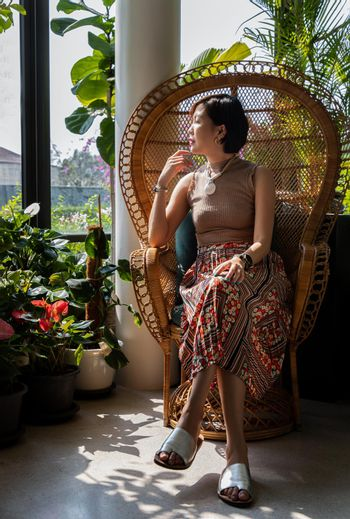 A young asian woman sitting and relax on peacock wicker rattan chair near glass window in living room. Selective focus.