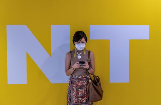 Close-up shot of young asia woman wearing face mask and using a smart phone typing text message while standing in front of yellow wall background during N and T letters. Wears face mask for the coronavirus pandemic. Selective focus.