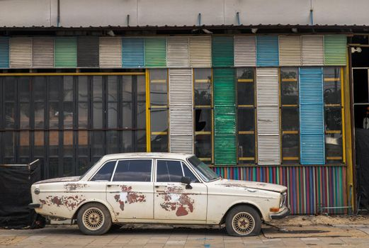 Bangkok,Thailand - May 20, 2021 : A broken and old vintage car were left at the side of warehouse. Selective focus.