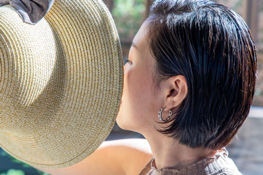 Young asian woman and short hair holds the brim of the Hat close-up. Selective focus.