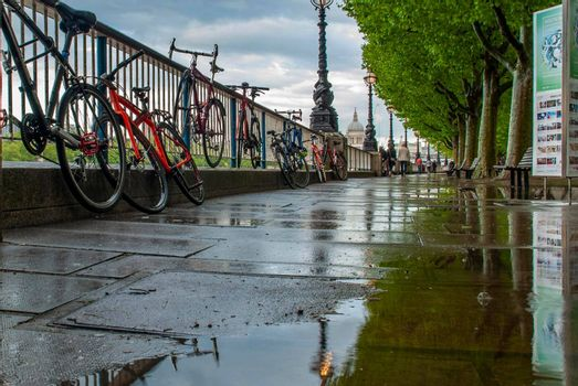 LONDON, UK - MAY 2, 2019 : Reflections in the water of the path banks of the River Thames after rain. Suitable for background images.