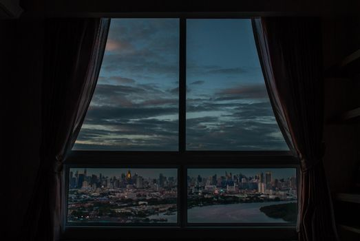 Bangkok, Thailand - 27 Aug, 2019 : The beautiful view of Bangkok, the beautiful skyscrapers along the Chao Phraya River in the evening seen through a bedroom window.