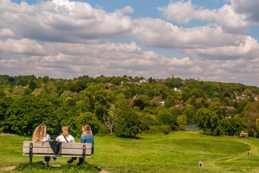London - May 21, 2019 - A womens sit on a wooden chair at Hampstead Heath with a beautiful city view backdrop.