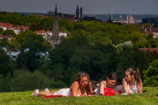 London - May 21, 2019 - Girls resting on a bright day at Hampstead Heath with a beautiful backdrop of the city.