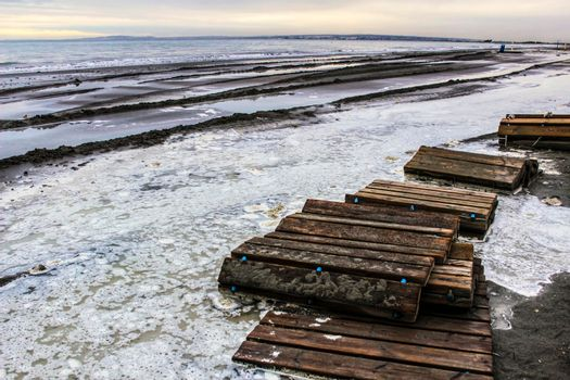 Beach flooded after the storm and broken wooden walkway in Alicante, Spain