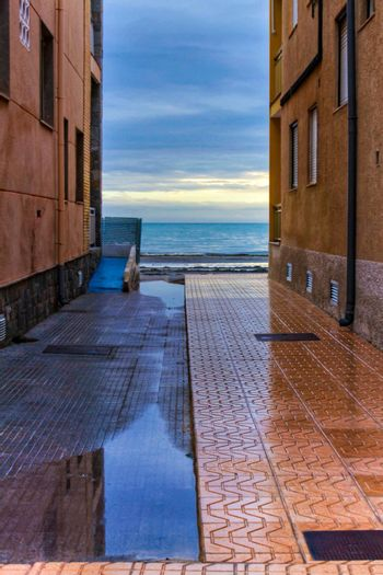 Lonely Little street between buildings facing the sea after a rainy day