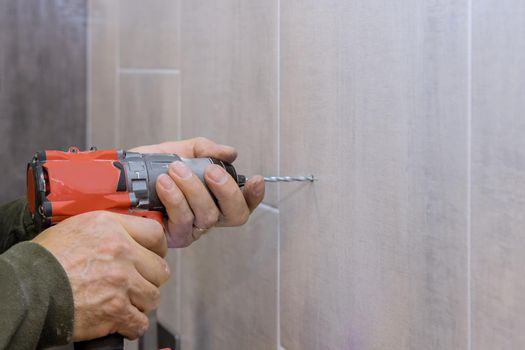 Hands of plumber using a drill to create new holes in tile bathroom wall for installing bathroom accessories