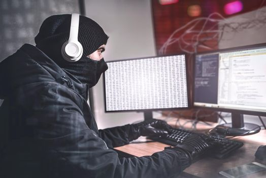 Teenage Hacker man Using her Computer to Organize Malware Attack on Global Scale. She's in Underground Secret Location Surrounded by Displays and Cables.
