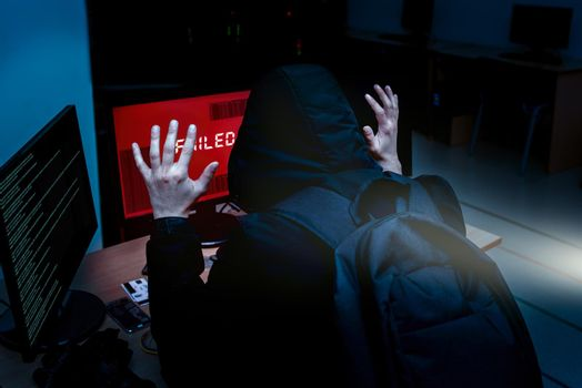 Internet criminal hacker trying to hack into corporate servers arrested by police at night. Portrait of a surrendered computer hacker who raised his hands under a flashlight. failed hack