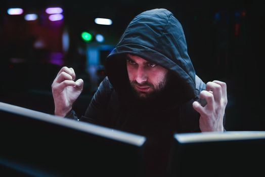 A male hacker in hood experiences angry emotions over a failed hack, the concept of a hack.