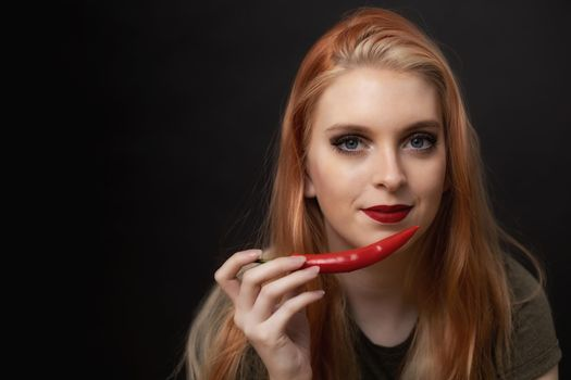 Portrait of beautiful young woman tasting chili pepper