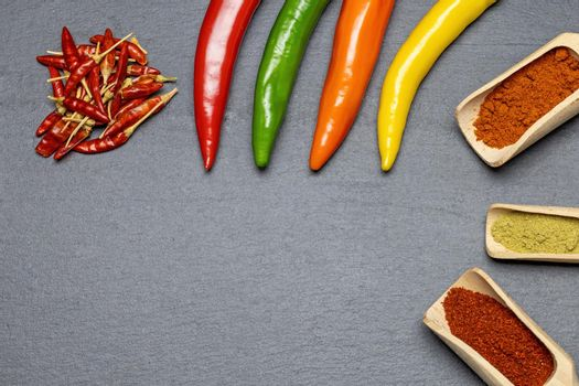 Different types of fresh, dried and ground chili on the desk.