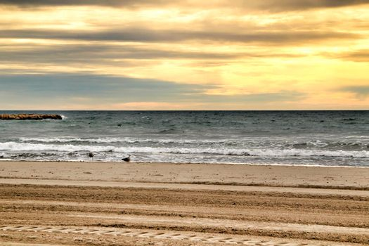 Beach under golden stormy sky in Santa Pola, Alicante, Spain