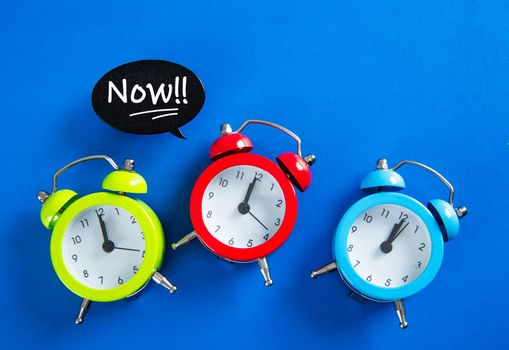 Speech bubble with  the word NOW on alarm clock on blue background with copy space,