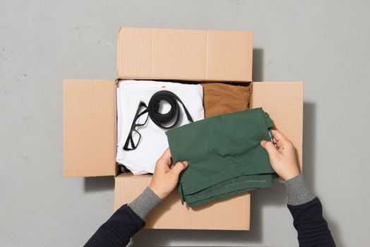 Man hands putting clothes to donate box