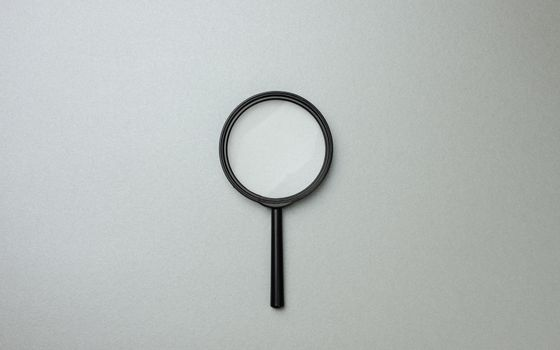 black magnifier on a gray background and question marks. The concept of uncertainty and the search for solutions