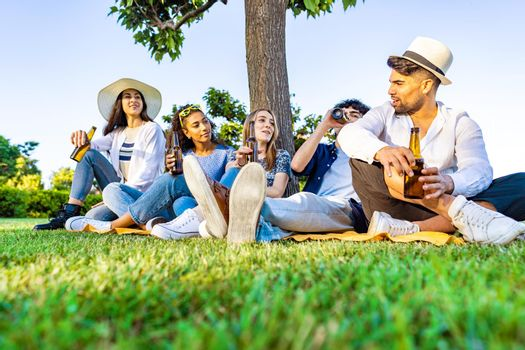 Group of five happy young diverse multiracial gen z people in outdoor party drinking beer from bottle talking each other sitting on grass of city park meadow. Friends having fun with alcohol outdoor