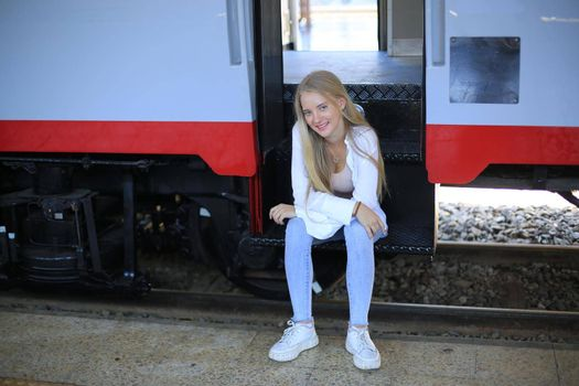 young woman waiting in vintage train, relaxed and carefree at the station platform in Bangkok, Thailand before catching a train. Travel photography. Lifestyle.