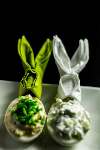 stuffed eggs with hand-made filling and bunny napkin, healthy and tasty snack