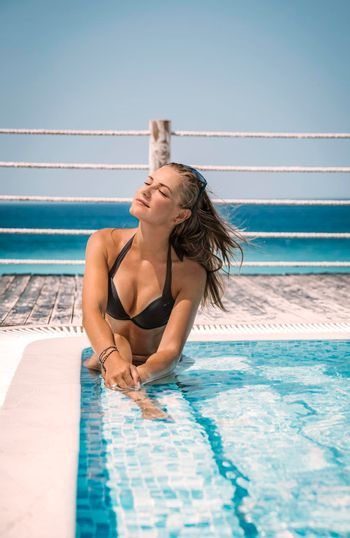 Beautiful Woman Relaxing in the Swimming Pool. Tanning on the Sun in Luxury Beach Resort. Enjoying Summer Vacation.