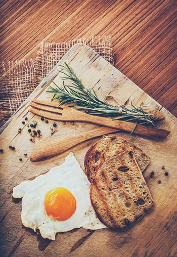 Breakfast. Tasty Fried Egg with Two Slice of Bread Decorated with Rosemary Branches an Served with Wooden Utensil and Canvas Napkin. Rustic Style.