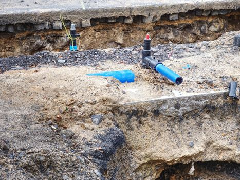 Blue steel water branch pipe installation in excavated trench
