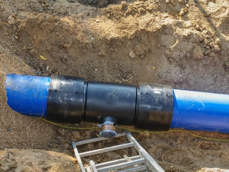 Blue plastic tubes in trench welded together with plastic pipes