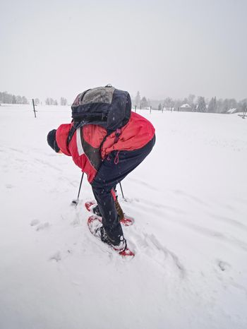 Snowshoe hiking in land. Active outdoor man hikes in farm range