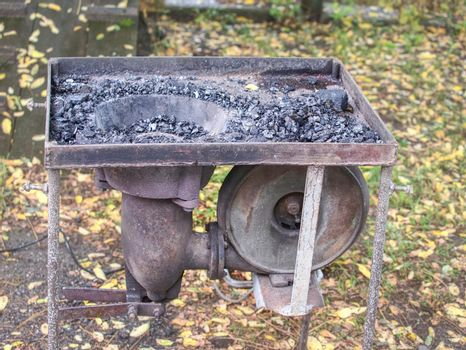 Farriers open portable furnace. Burning coal in the furnace
